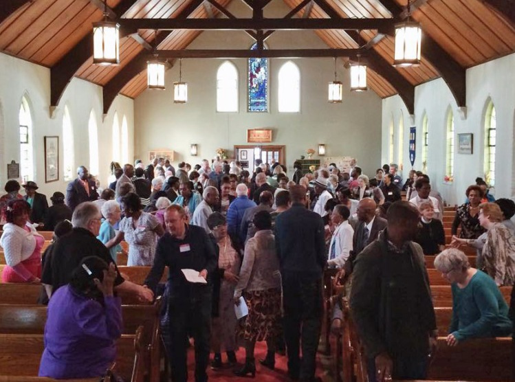 "St. Mary and Martha Church, Mount Dennis, Toronto, passing the peace at their first Eucharist as an ""amalgamated"" congregation last October. (parish photo)"