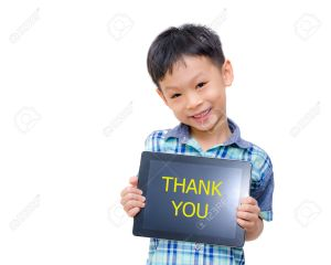 Little asian boy smiles with tablet computer on white background