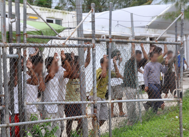 The government of Australia, after insisting that world criticism of its immigration and detention policies would would not change them, has now decided to close its detention center on Manus Island, Papua New Guinea, where 800 asylum-seekers have been held indefinitely in horrible conditions, as seen above in 2014 with faces pixillated. Their crime: trying to get to freedom. Recent reports from human rights organizations say the government has condoned thousands of sexual assaults on women and children to discourage anyone else from trying to escape their misery. (Eoin Blackwell/AAP via Reuters)