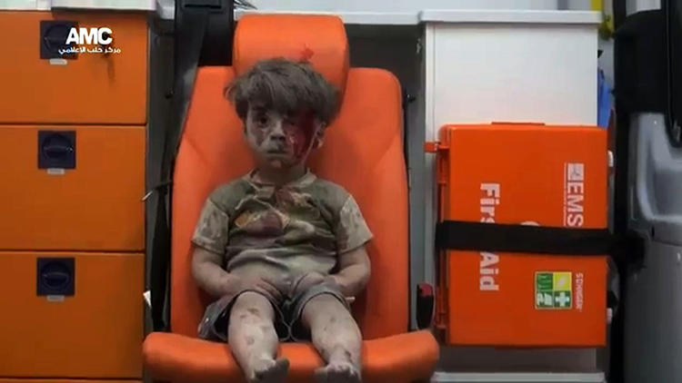 His name is Omran. He's from Aleppo; that's in a place called Syria. He doesn't understand why his house was blown up and hurt his entire family; or why grownups shoot and kill and bomb each other. He doesn't understand at all. But he has cried so much that now he can't think or feel anything; and neither can anyone else.