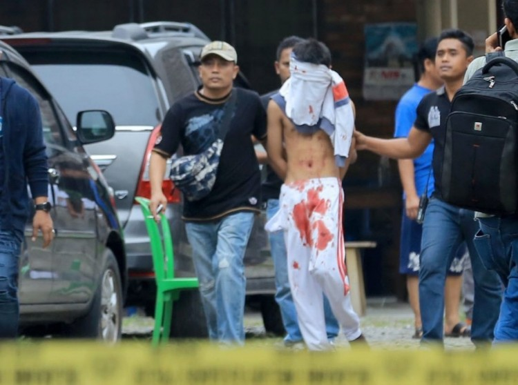 This fellow attempted to bomb a Roman Catholic church in Medan, Indonesia yesterday in the middle of Mass, but his bomb fizzled, he ended up hurt and police hustled him away. It's the second terrorist incident this year in the world's biggest Muslim nation, which also has a sizable Christian population. (Dedi Sinuhaji/Euro Pressphoto)