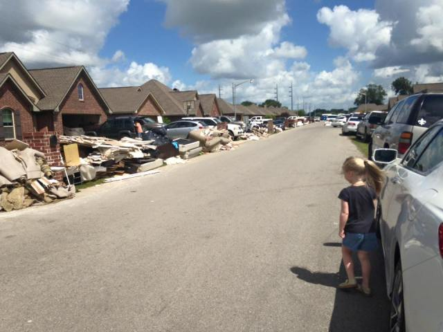 """An unidentified subdivision in Cajun Country in South Louisiana on Tuesday, after widespread flash floods killed 11 people and caused a billion dollars in damage: I can almost hear this child say, """"Until a few days ago, this was our stuff. This was everybody's stuff."""" (Ella Raven Photography)"""