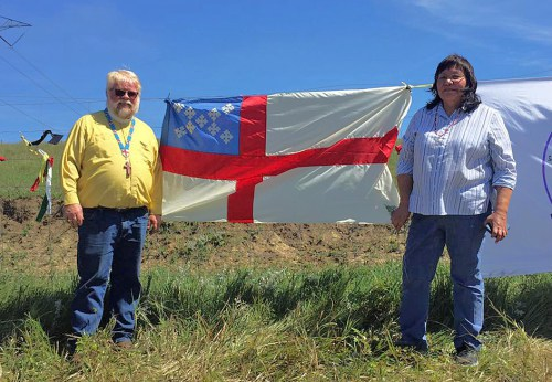 The Episcopal Church flag joined the banners of other pipeline opponent groups tied to the fence near the construction site, with the Rev. John Floberg and Carmine Goodhouse representing St. Luke's, Fort Yates, North Dakota. (The Rev. John Floberg via Episcopal News Service)