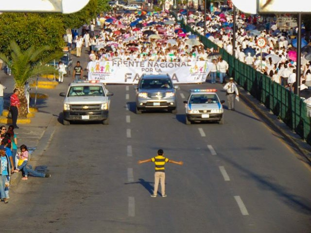 "A 12-year-old boy stopped traffic last weekend in Celaya, México, where an anti-Gay march was being held by the National Front for Families, one of several such demonstrations around the nation. Was he just wanting attention? Playing? Leading the march? No, he was trying to stop it, he said; ""I have a Gay uncle and I don't like people spreading hate about him."" Within hours, this photo went viral. (Manuel Rodriguez/RegeneraciónMx)"