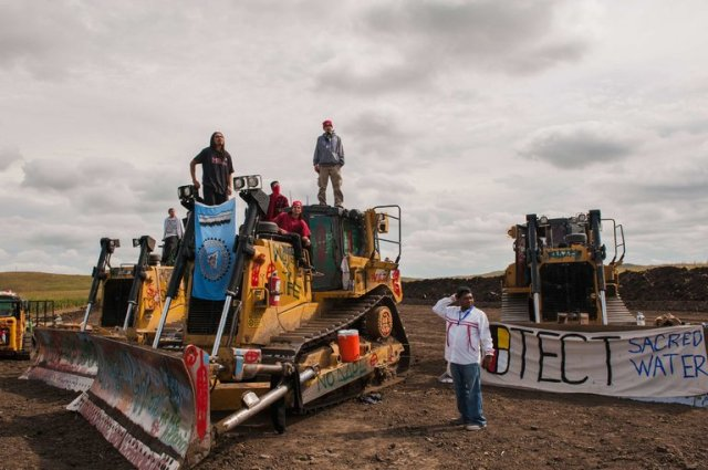 Native American activists from all over the continent have rallied behind the Lakota Sioux of the Standing Rock Reservation in North Dakota, trying to prevent construction of a big oil pipeline right outside their property line. They were accused by the local sheriff of various crimes, like painting peace messages on bulldozers; meanwhile the pipeline's security company deployed snarling dogs and pepper spray. The Indians' uniquely spiritual relationship with the land is threatened; whatever happens, Protect Sacred Water. (Andrew Cullen/Reuters)