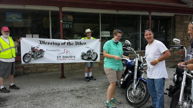 The Rev. Kelsey Hutto of St. David's, Bean Blossom, Indiana, blessing motorcycles at the Brown County town's annual BikeFest this weekend; elitist Anglican snobs, every one of them. (Marylin Day)
