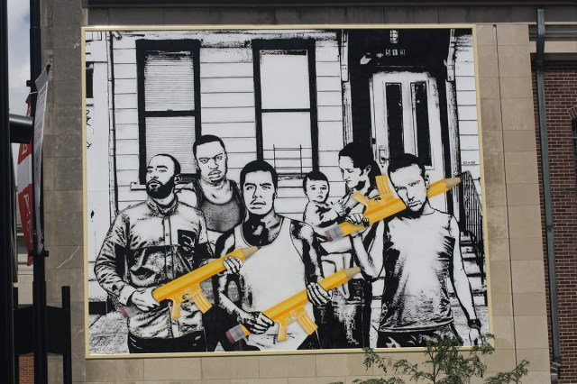 Christ Church Cathedral in downtown Cincinnati, concerned about gun violence and murders, teamed up with a youth program called ArtWorks Cincinnati to produce this poster, hung on the side of the church. Those aren't AK-47s the young men are toting, they're big pencils like you can draw with. (Sarah B. Hartwick)