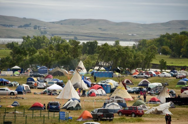 An impromptu tipi village has sprung up on the Standing Rock Indian Reservation in North Dakota, a mile from the construction site of the proposed Dakota Access oil pipeline, which the Lakota Sioux and hundreds of other Native American tribes are protesting. The pipeline was originally supposed to be built just north of the state capital, which rebelled against it out of fear for the water supply; so the builder moved the route right next to the indigenous people's reservation, figuring they were too poor and powerless to do anything about it. Many of the Standing Rock members are Episcopalians. (Robyn Beck/Agence France-Presse)