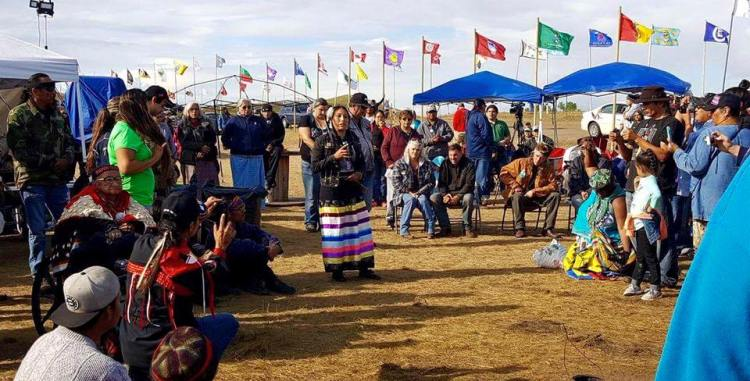 Standing Rock declares victory: the U.S. government announced yesterday that it was halting construction of a billion-dollar oil pipeline under a major river at the edge of the Standing Rock Indian Reservation in North Dakota; here we see the news delivered by a Lakota Sioux leader to hundreds of protesters. This is far from a final outcome; earlier in the day a Federal judge refused to grant the Indians' request for an injunction to block construction. Instead, the government called for a serious national discussion with tribal leaders about their religious, cultural and safety complaints concerning big infrastructure projects, and suggested that new legislation may be needed to recognize tribal rights. The Standing Rock protest has been hailed as the biggest show of American Indian unity in over a century, as each flag above represents an Indian nation present to support the Lakotas. (The Rev. Lauren R. Stanley)