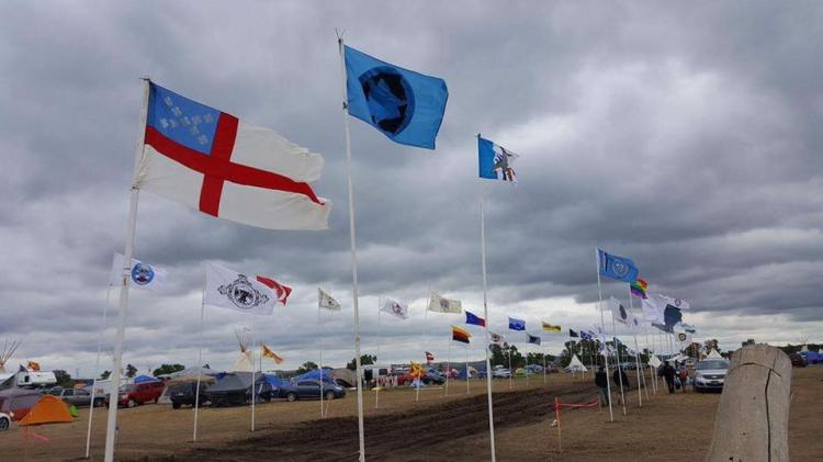 The Episcopal Church flag among the banners of many nations at the Standing Rock Indian Reservation near Cannon Ball, North Dakota, where hundreds of Native American tribes have protested the building of an oil pipeline just a stone's throw from reservation-owned land. Historically, reservation boundaries were drawn as narrowly as possible by the government to impoverish the People and maximize the profits of whites; then if minerals or other assets were discovered on Indian land, the government simply took it back again by military force. All of Oklahoma was once reserved for Indians; then whites decided they wanted that land too, so the government changed the law and Oklahoma suddenly turned white. (The Rev. Lauren R. Stanley)