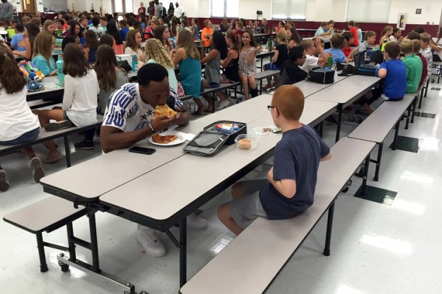 """Members of the Florida State University American-football team traveled to a local middle school in Tallahassee this week as a goodwill gesture, but something happened that made the visit more than routine. One of the players noticed a boy in the lunchroom sitting by himself, and asked if he could sit with him. The boy looked up and said, """"Sure, why not?"""" He didn't know that the tall athlete standing there was Travis Rudolph, one of the stars on the highly regarded team, and the athlete didn't know that the kid was named Bo Paske, who is diagnosed on the autism spectrum. But they soon found out, and so did the rest of the world, when Bo's mother was moved to tears by the big man's kindness and posted her thanks on Facebook. Bo has friends and sometimes eats with them, but other times he sits by himself. (Michael Halligan)"""