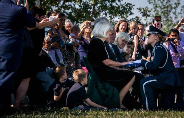 Elaine D. Harmon, a veteran of the U.S. Women Airforce Service Pilots in World War II, was finally laid to rest this week at Arlington National Cemetery, after a decades-long battle to win full military rights and honours. The WASPS, about 800 trained and sworn pilots, performed vital training and logistical services to the military, freeing up male pilots for fighting. But because they were women, they were never allowed to join the military officially; they did the work (and assumed the dangers) of military pilots without the money, support, recognition or privileges that come with it. The USA was reportedly worried that Japan would make fun of them for using women pilots. For political reasons promises made weren't kept, the WASPs' very existence was classified, their cause was forgotten, and it took the women themselves to forcefully persuade the top brass to give them full recognition. The final hurdle was the right to be buried in a national cemetery; above, a sworn woman officer kneels to present Old Glory to Terry Harmon, Elaine's daughter. Rest in peace, Captain Harmon, for a job well done. (Gabriela Demczuk/The New York Times)