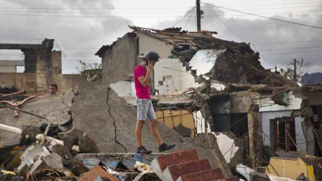 A young man in Baracoa, Cuba, making a call amid the rubble of his home after Hurricane Matthew. (Ramon Espinosa/Associated Press)