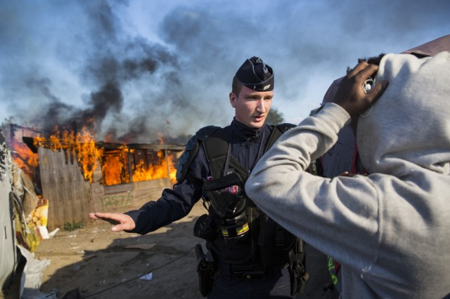 """A police officer controls the crowd Monday while behind him officials set fire to """"The Jungle"""" refugee camp at Calais, France, where about 8000 Afghan and African refugees, many of them unaccompanied children, have lived while they hoped to get asylum in Britain. British civilians, not the French, provided food, clothes and social services to the migrants; some were more than ready to leave, but others will miss the little bit of home they were able to create. Most of the refugees are being dispersed throughout the French countryside, often to towns where people don't want them and are greeting them with jeers and taunts. (Jack Taylor/Getty Images)"""