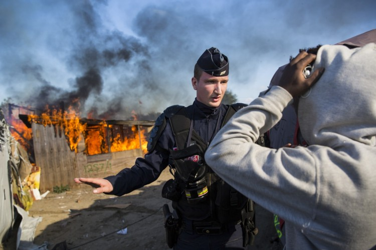 "A police officer controls the crowd Monday while behind him officials set fire to ""The Jungle"" refugee camp at Calais, France, where about 8000 Afghan and African refugees, many of them unaccompanied children, have lived while they hoped to get asylum in Britain. British civilians, not the French, provided food, clothes and social services to the migrants; some were more than ready to leave, but others will miss the little bit of home they were able to create. Most of the refugees are being dispersed throughout the French countryside, often to towns where people don't want them and are greeting them with jeers and taunts. (Jack Taylor/Getty Images)"
