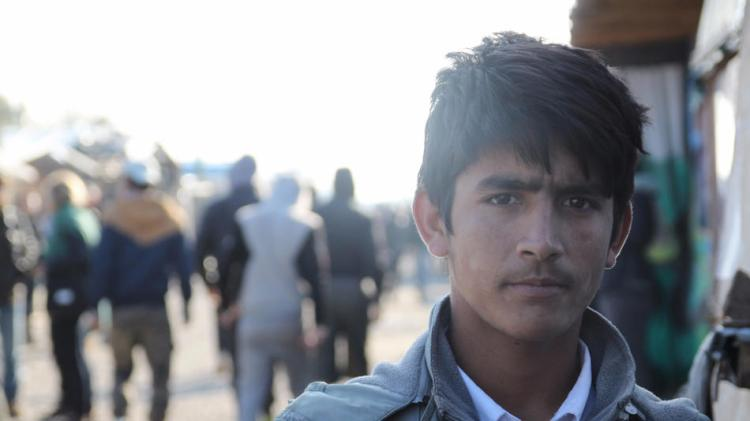 """The French government started demolishing """"The Jungle"""" at Calais yesterday, destroying the squalid camp where Syrian, Afghan and other refugees hoped to catch a ride to the United Kingdom. But as bleak as conditions were, the camp was also a supportive community of like-minded people, many of them unaccompanied children like Afsar Khadarkhail, 12, of Afghanistan; local volunteers built a ramshackle teen hangout with a pool table, television and mobile phone charging stations. The French say they will relocate some residents elsewhere within the country, while others will be paroled to Britain, where most want to go. Those held back in France may try to escape by stowing away on a passing vehicle headed for the Channel Tunnel; some have reportedly made it to Britain, but others have been killed on the way. (Matt Tinsley/Los Angeles Times)"""