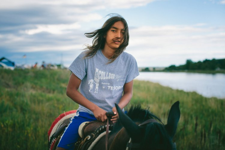 Charles Baker, 13, at the oil pipeline protest on the Standing Rock Indian Reservation last month in North Dakota; he is Lakota and Swinomish from Washington State. In the background is the Missouri River, longest in North America, which the pipeline is supposed to run under if it gets built; you can see how close it is to the campground, just outside the reservation fence. (Alyssa Schukar/The New York Times)