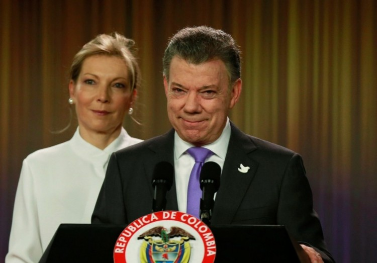 """Juan Manuel Santos, the president of Colombia, with his wife Maria at a news conference at the Narino Palace in Bogotá Friday after he won the Nobel Peace Prize for trying to end his country's 52-year-long civil war, an agreement narrowly rejected Sunday by Colombian voters, who think the FARC rebels should be imprisoned instead of set free. The referendum's failure tipped the scales toward renewed violence, but with a Nobel and the world's approval in his hand, Santos may be back in the driver's seat. Meanwhile, major American newspapers are reporting today that many """"no"""" voters were motivated by an anti-Gay campaign promoted by Roman Catholic and fundamentalist leaders and right-wing politicians. (John Vizcaino/Reuters)"""
