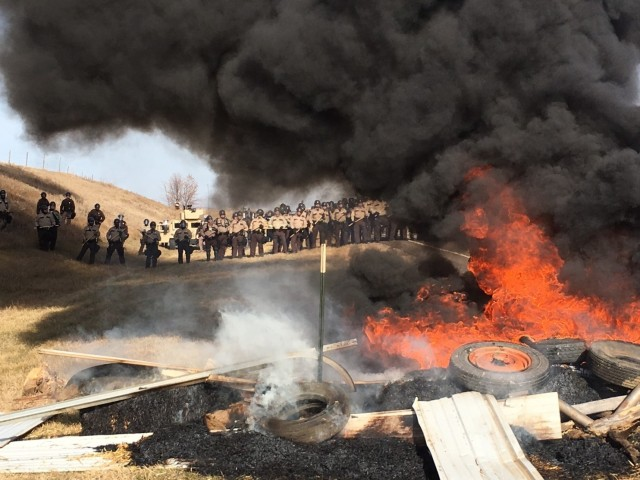 State and local police and members of the National Guard stood in formation yesterday as they cleared out Native Americans protesting the Dakota Access Pipeline; dozens were arrested and one man was hurt. The fire was reportedly started by protesters attempting to block the road and slow down the soldiers and police, who cleared an area owned by the pipeline company north of the protesters' main campground on the Standing Rock Indian Reservation near Cannon Ball, N.D. (Mike McCleary/The Bismarck Tribune)