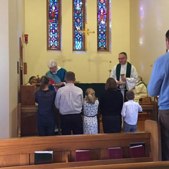 A family communes at St. Andrew's, Greencastle, Indiana during Bishop Cate's last visit. (Sean Sullivan)