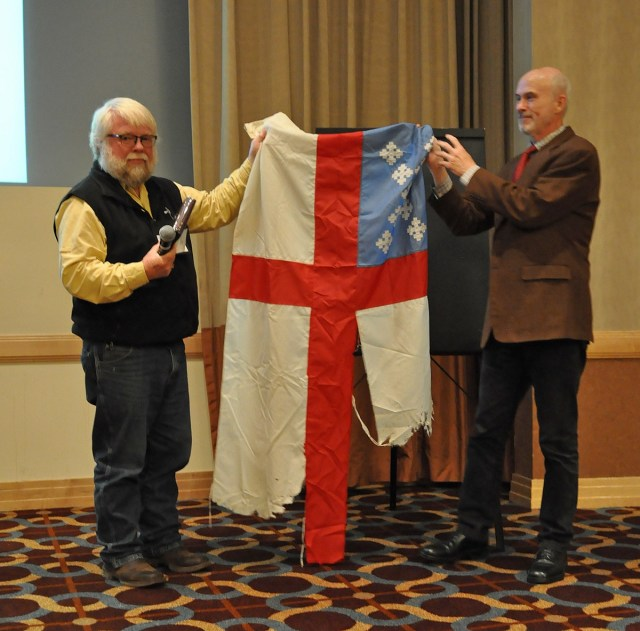 The Rev. John Floberg, left, missionary priest at the Standing Rock Indian Reservation in North Dakota, presented an Episcopal Church flag which flew over the campground where Native American protesters are trying to stop construction of a big oil pipeline right next door, to an official of the Episcopal Church Archives last week at a meeting of the Episcopal Church Executive Council. The flag, whipped by the fierce winds of the Great Plains, was the only church flag to fly over the camp, along with hundreds of flags representing many of the First Nations of North America. The protests continue, with scores of people arrested over the weekend. The Indians plan to keep up their vigil all winter if need be until the bulldozers are loaded up and hauled away. (The Rev. Mary Frances Schjonberg/Episcopal News Service)