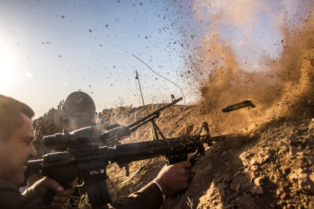 The battle for Mosul, Iraq began overnight, with enormous destruction expected as Iraqi forces try to oust the so-called Islamic State. Above: Kurdish peshmerga fighters take aim at ISIS. (Bryan Denton/The New York Times)