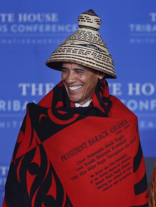 "We don't publish many U.S. presidential photos, but this one is noteworthy, and not just because of his fine-looking hat. Barack Black Eagle Obama (his Crow name in English) is wrapped in an honorary red and black blanket, ""sharing our symbol of love, comfort and protection."" (His full name in Crow is Awe Kooda Bilaxpak Kukshish, or One Who Helps People Throughout The Land.) He convened his eighth and last annual White House Tribal Conference last week with a record of accomplishment many Native leaders say is the best in U.S. history, with billions of dollars in settlements finally paid on century-old Indian debts. The government was supposed to act as the tribes' bookkeeper for land rents and royalties, but kept the money for itself and failed to account for it, leaving a legal mess for future generations to sort out. With some monies finally paid (though much remains), let us pray the tribes will invest wisely; after 100 years they certainly can use the money. (Pablo Martinez Monsivais/Associated Press)"