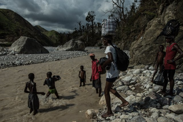 As if Rendel, Haiti didn't have enough to deal with, deadly cholera has combined with Hurricane Matthew to wipe out 90% of the town of 25,000. Most survivors have fled, but those escaping have to cross this contaiminated river multiple times; the only community leaders left are the Roman Catholic priest and a few nurses who run a clinic that's fast running out of supplies. (Meredith Kohut/The New York Times)