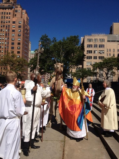 The Bishop of New York Andrew Dietsche blessing a camel on St. Francis's Day at the Cathedral of St. John the Divine, 2014. (cathedral photo)