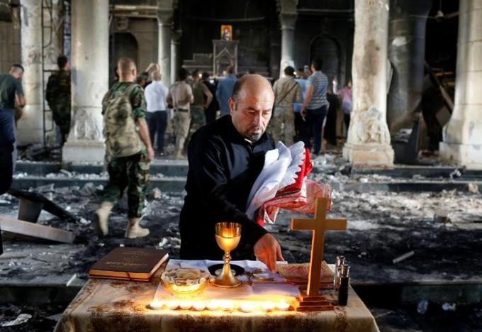 Here we can see the interior damage to the church in Quarqosh, as a priest gathers up the holy things after the Divine Liturgy. (Ahmed Jadallah/Reuters)