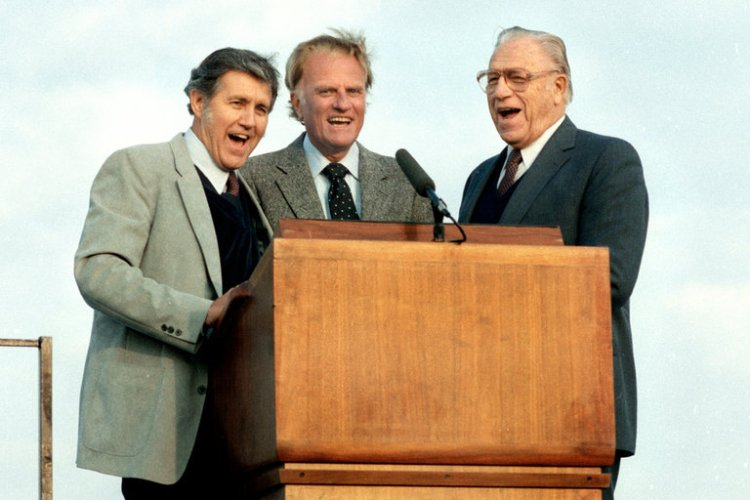 Cliff Barrows has died, Billy Graham's longtime musical director and a radio preacher in his own right. They met at Bob Jones University, found their skills were complementary, and merged their ministries so that Graham preached and Barrows' choirs sang for over 200 million people in 183 countries for 58 years. Above: Barrows, Graham and vocalist George Beverly Shea, singing at the podium together during a crusade in Dallas, Texas in 1987. (Billy Graham Evangelistic Association)