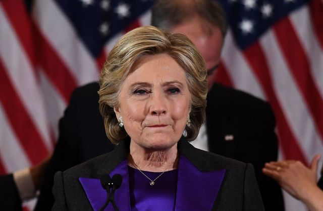 """Hillary Rodham Clinton at her concession speech a few hours ago, with running mate Tim Kaine behind her. The defeat is painful, she said, but her supporters owe the U.S. President-Elect """"an open mind and a chance to lead."""" (Jewel Samad/Agence France-Presse)"""