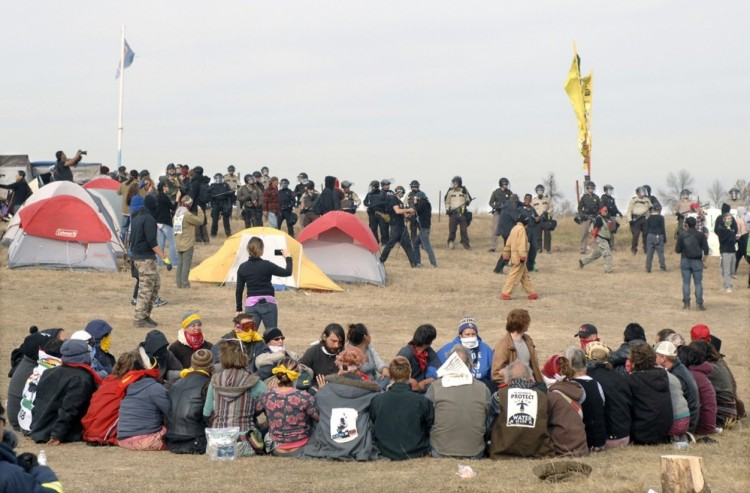 Police and soldiers from the National Guard advancing on a prayer circle at Standing Rock Indian Reservation in North Dakota last week, where thousands of protesters have camped out for months trying to prevent construction of an oil pipeline across land that once was theirs, until the U.S. government broke a treaty and stole it back. The land is now owned by the pipeline company and runs through ancient burial grounds right next to the current reservation; besides disturbing the ancients, they fear the pipeline will break and contaminate their only source of drinking water, the Missouri River. The power struggle is growing more violent; 140 people were arrested. The Episcopal Church, which has historic churches among the Standing Rock Lakotas, is solidly behind relocating the pipeline and respecting the sacred land. (Mike McCleary/Bismarck Tribune)