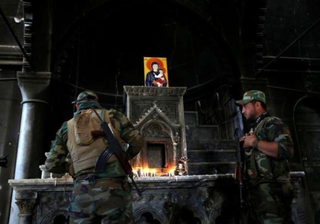 An Iraqi Christian soldier lights a candle after Mass at Qaraqosh. (Ahmed Jadallah/Reuters)