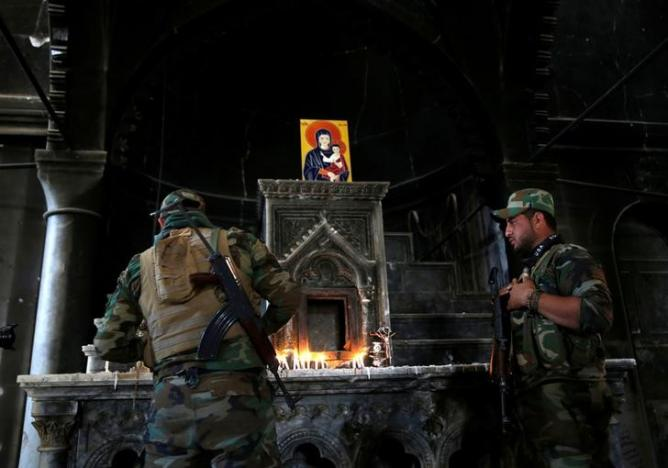 An Iraqi Christian soldier lights a candle after Mass at Qaraqosh. (Ahmed Jadallah/Reuters)