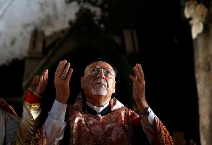 The Syriac Catholic archbishop recites the Eucharistic prayer during the first Mass at Immaculate Conception Church since it was recaptured from ISIS in Qaraqosh, near Mosul, Iraq, two Sundays ago. The building was heavily damaged during the occupation, but they carried on in faith. (Ahmed Jadallah/Reuters)