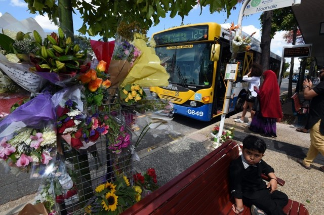 """Flowers decorated a bus stop near Brisbane, Australia last weekend after a bus driver was killed and 11 passengers were injured when a man threw a molotov cocktail on the bus. The well-liked driver, Manmeet Alisher, 29, was an immigrant from Punjab, and suspicions were quickly raised that it might be a hate crime. A man was soon arrested, and has been described in media reports as an """"erratic loner,"""" which may cast doubt on the anti-immigrant theory; either way, what a tragedy to lose this young man, making his way successfully in a new country. (Dan Peled/European Pressphoto)"""