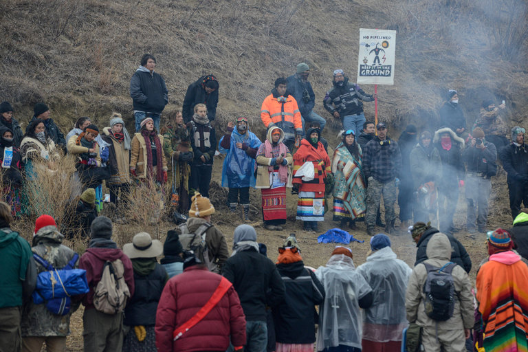 """The U.S. Army Corps of Engineers announced plans on Friday to close the Standing Rock oil pipeline protest camp, citing increasing violence between police and protesters. They want to move the Lakota Sioux demonstrators and their Native allies in 300 other tribes to a more convenient """"free speech zone"""" that allows traffic to move. But this isn't likely to work; the Indians took the bridge for a reason, to disrupt the pipeline construction right next to their reservation and underneath their water supply. Standing Rock Chairman Dave Archambault II says the way to defuse the confrontation is to move the pipeline. Last week hundreds of demonstrators were injured, including one critically, in what looked like a police riot; the county sheriff has sided with the pipeline company and the white neighbors. (Stephanie Keith/Reuters)"""