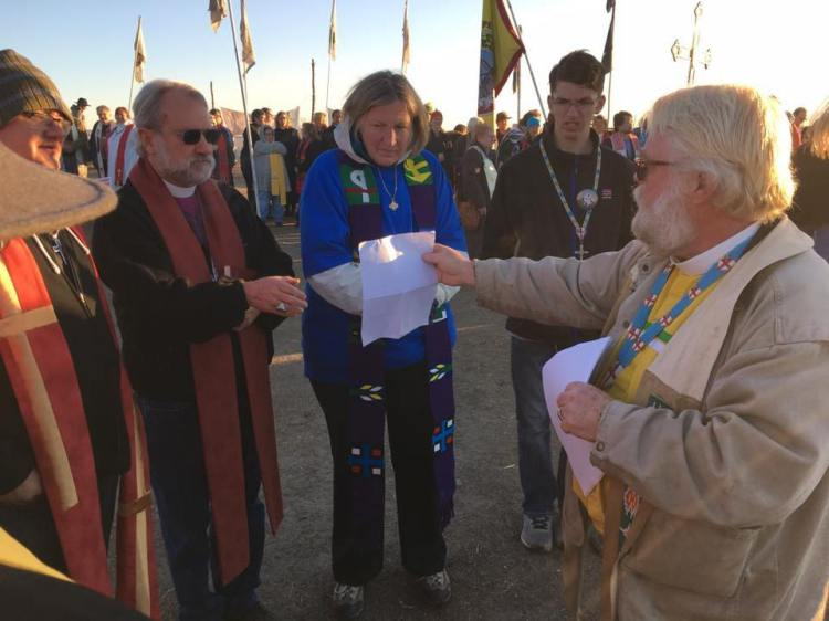 "The Rev. John Floberg, right, supervising priest on the Standing Rock Reservation in North Dakota, hands out a document repudiating the Doctrine of Discovery on Thursday as part of a march by over 500 clergy and lay leaders of various denominations supporting the Lakota Sioux's effort to block construction of an oil pipeline a mile from their water supply. The bishop read the statement, then gave it to tribal leaders and watched them burn it. The Episcopal House of Bishops approved a resolution in 2009 condemning the theological and legal theory of the 15th Century that tried to justify European Christian imperialism, slavery and theft: ""if you 'discover' it, it's yours."" (The Rev. Lauren Stanley)"