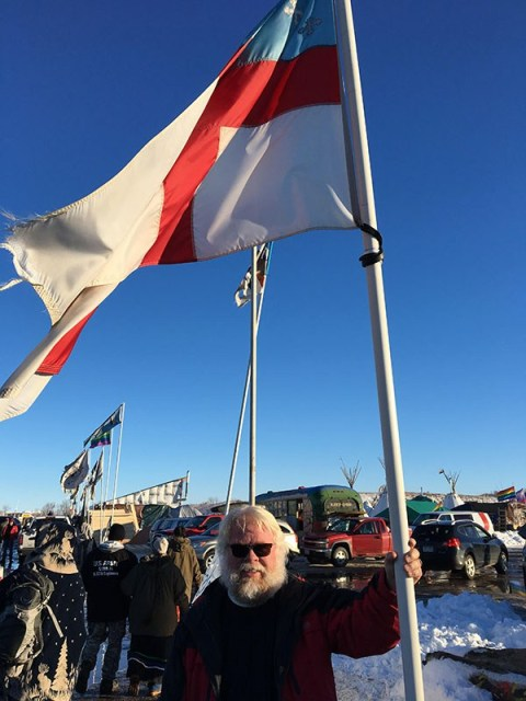 The Rev. John Floberg with a wind-battered Episcopal Church flag at Standing Rock Indian Reservation Monday, the day after the U.S. Government refused to issue easements needed to complete a large oil pipeline a mile from the reservation. Fr. Floberg, the supervising priest in the North Dakota portion of the reservation where 7 months of anti-pipline demonstrations have taken place, is also a member of TEC's national Executive Council, and has become the voice of the Church during the pipeline controversy. He is one of many responsible for a tremendous victory by indigenous peoples the world over who united to back Standing Rock's cause. (The Rev. Lauren R. Stanley)