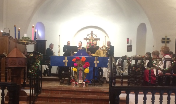 Mariachi players around the altar yesterday at St. Clement's By-the-Sea in San Clemente, California, for their annual Virgen de Guadalupe celebration, with a rose-bedecked shrine in front. (Katrina Soto)