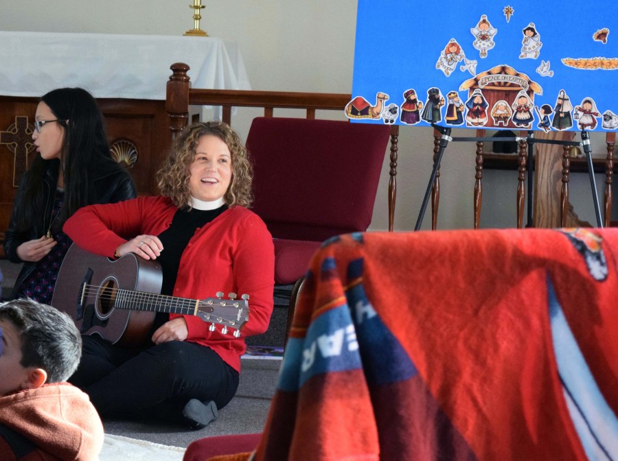 """The Rev. Sarah Quinney, music therapist and assistant priest at St. John's in nearby Roseland, California, provided music and clinical expertise for the special-needs party at St. James's. """"Does anybody want to hear a story?"""""""