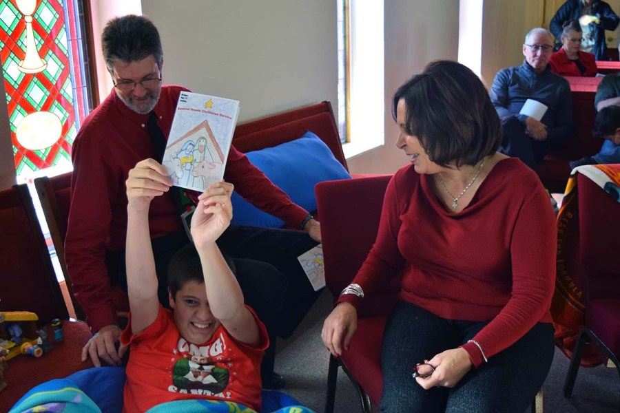Braden Johnston shows off the cover art he drew for the Christmas program at St. James's, Lincoln, as parents Drew and Maria look on with pride.