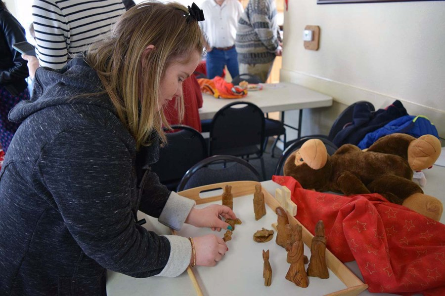 You can no more have a Christmas party without a Nativity scene than you can have one without giant stuffed monkeys. So Emily Rhoads, who helped with the service, sets up the manger as a nearby monkey takes a nap.