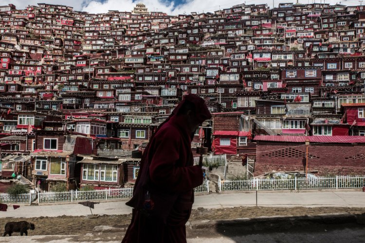 A Buddhist nun spins a prayer wheel as she passes thousands of hand-built cells surrounding an influential monastery in Sichuan Province, China. Government bulldozers are now tearing them down in China's constant effort to suppress religion, but people are still building their little booths. Christian monasteries developed in much the same way; a solitary hermit would find a cave and go into hiding to pray, then other people would find out and want what that person had. This, however, is an extraordinary response. (Gilles Sabrié/The New York Times)