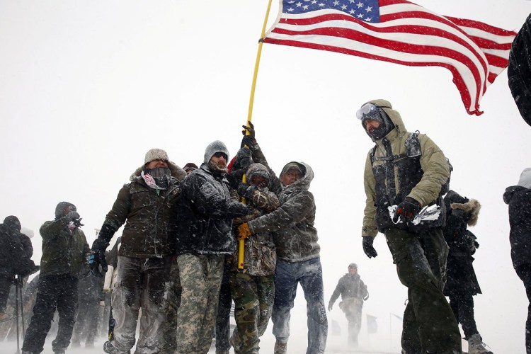 Veterans marching in the snow to Backwater Bridge near Standing Rock Indian Reservation Monday, a day after the U.S. Army Corps of Engineers said it would not issue permits to complete a giant oil pipeline opposed by the Lakota Sioux tribe. The veterans' arrival, hundreds strong, was credited by many with tipping the balance toward accomodation, after months of protests and increasing violence by police and heavily armed private security. (Lucas Jackson/Reuters)