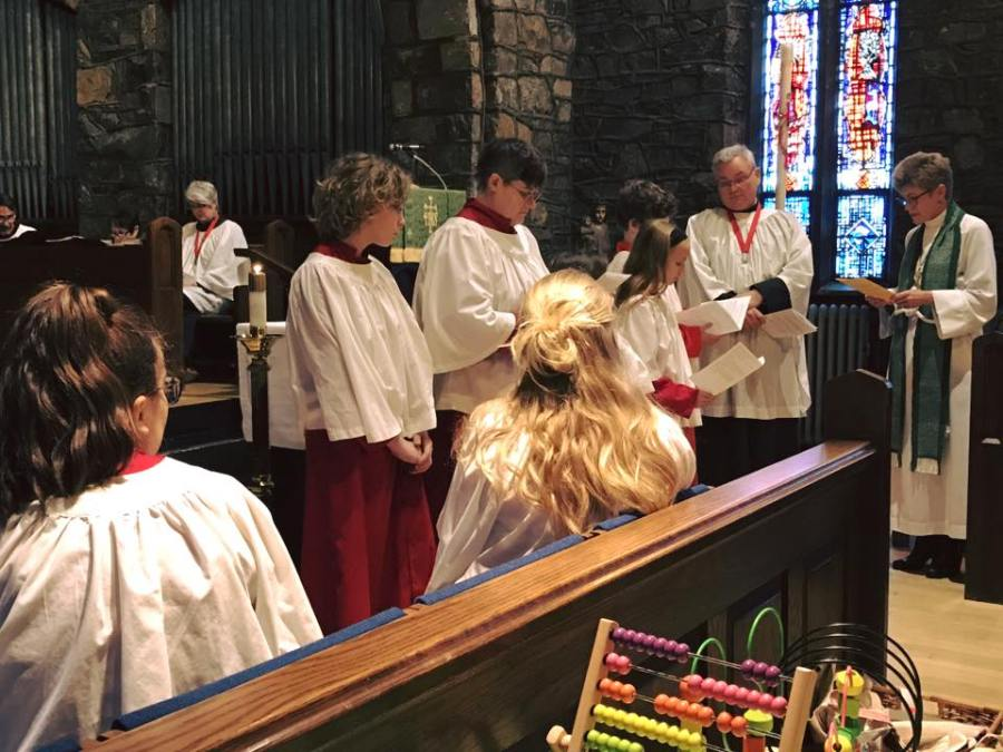 Acolytes were commissioned on Sunday at Grace Church, Brunswick, Maryland, by the rector, the Rev. Anjel Scarborough, with Senior Warden Al Horton keeping an eye on them. We know their names – Jordan, Christina, Miriam, Millie and Gabriel, and we can see four of them – but Miriam, who isn't very tall yet, is hidden by the crucifer in the foreground. (Notice also the toys.)
