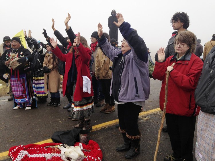 A state representative in North Dakota named Keith Kempenich has introduced a bill to legalise running over protesters who block highways, aimed at Native Americans and others at the Standing Rock Indian Reservation. Water protectors, as they style themselves, have engaged in a yearlong peaceful demonstration to prevent a giant oil pipeline from being built under the Missouri River just outside the reservation's current borders, on land that was once guaranteed to them by the U.S. government, until the white people stole it back again. Kempenich claims his elderly mother was surrounded and intimidated one day while driving past the site. He says that under his bill, the driver would still have to try to avoid hitting people, but if they accidentally kill someone it's not their fault. The Obama Administration has blocked the pipeline, but the white ranchers, whose ancestors stole the land 150 years ago, want revenge. (Sacred Stone Camp)