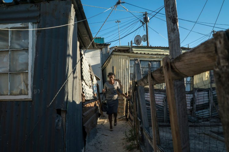 South Africa, faced with some of the world's worst income inequality, is considering establishing a minimum wage for the first time, though at such a low rate it would not benefit many workers, who also contend with housing segregation and high transportation costs. Khayelitsha, a vast township located between two wealthy white areas, provides an example; 23 years after ANC's revolution, blacks still earn one-fifth what whites do, and hunger is widespread. (Joao Silva/The New York Times)