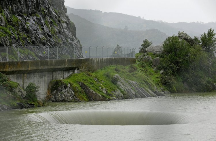 "After suffering through years of drought, California has received so much rain and snow this season that dams are being closely watched and reservoirs are threatening to overflow – except at Lake Berryessa, which has a giant ""glory hole"" spillway draining 150 cubic feet of water per second into the creek below, drawing onlookers, TV cameras and a sky full of drones. (Eric Risberg/Associated Press)"